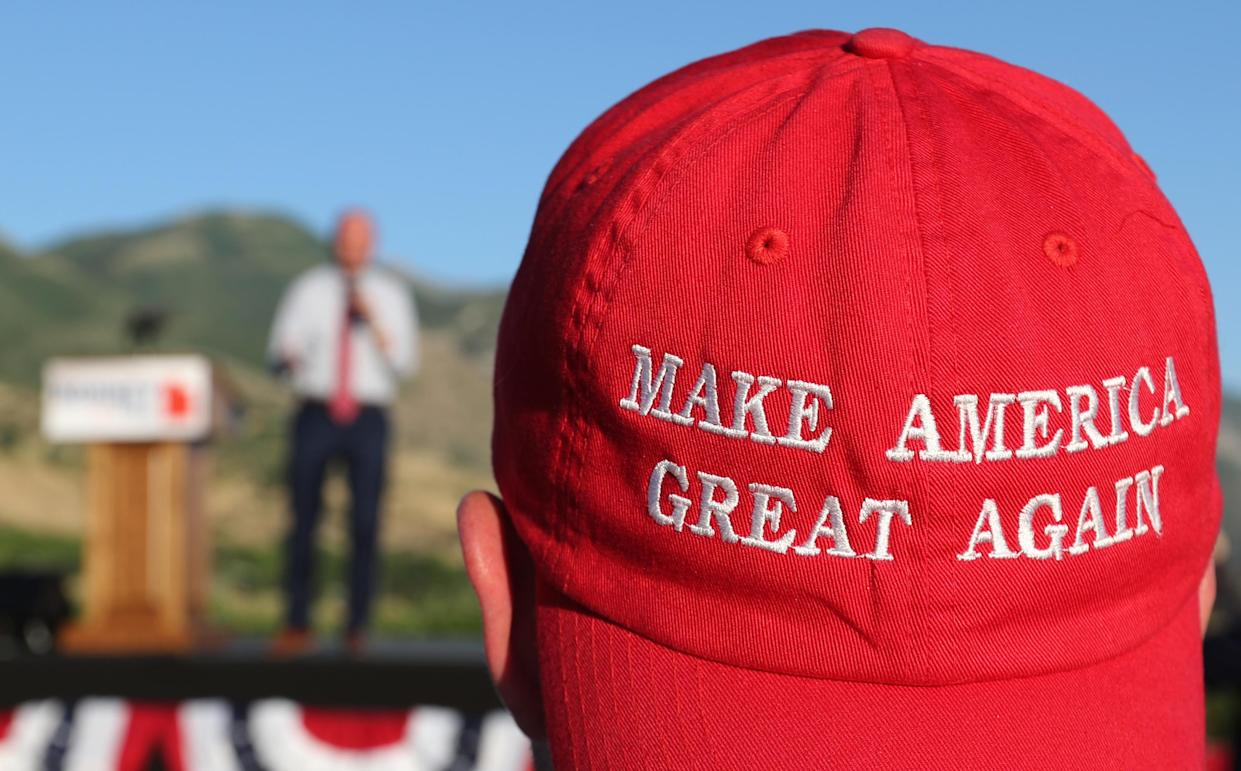 "A Romney supporter listens to a speaker as he wears a ""Make America Great Again"" hat at a Mitt Romney election party in Orem, Utah, June 26, 2018. (Photo: George Frey/Getty Images)"
