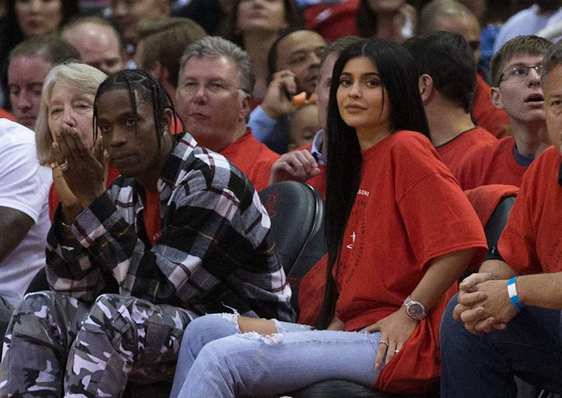 Kylie Jenner's rumored new beau, Travis Scott, here with her at a basketball game in April, is being sued for not paying a (big) bill.