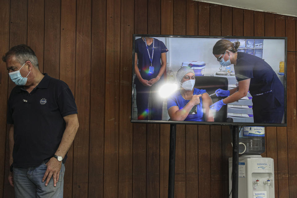 A monitor shows a live video image of nurse Zulema Riquelme getting the first shot of the COVID-19 vaccine at the Metropolitan Hospital in Santiago, Chile, Thursday, Dec. 24, 2020. The first batches of vaccines produced by Pfizer arrived today. (AP Photo/Esteban Felix)