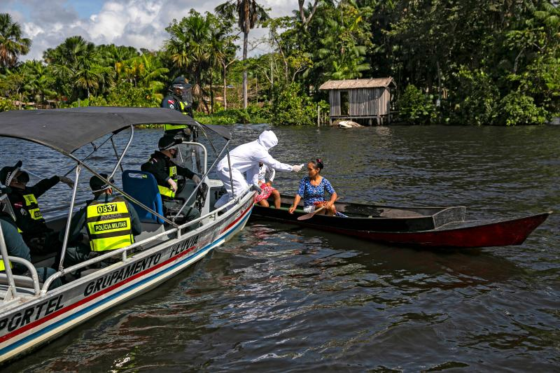 A government medical worker, in a joint operation with military police, checks a passenger on a boat in the Melgaco bay, southwest of the island of Marajo, Para state, Brazil, on May 27, 2020. - People onboard small boats, ferries and ships on the river had their body temperature checked as authorities try to combat the new coronavirus. (Photo by TARSO SARRAF / AFP) (Photo by TARSO SARRAF/AFP via Getty Images)