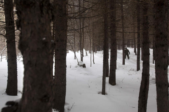 In this Wednesday, April 4, 2012 photo, a North Korean soldier walks through a forest that is said to be a camp site where the late North Korean leader Kim Il Sung spent the night while leading a battle against the Japanese at the foot of Mount Paektu. (AP Photo/David Guttenfelder)