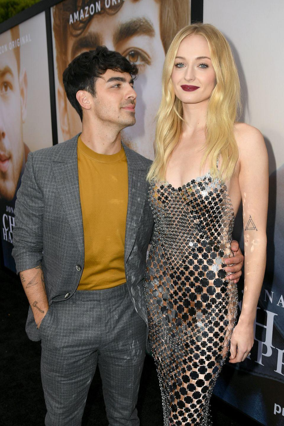 <p>Understandably, Jonas can't keep his eyes off Turner in this dazzling chainmail dress by Paco Rabane at the premiere of the Jonas Brothers documentary 'Chasing Happiness'.</p>