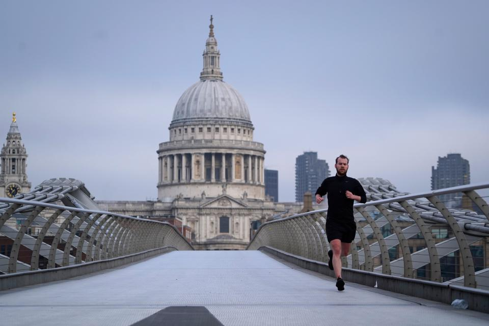 A jogger runs across the Millennium Bridge across the River Thames with St Paul's Cathedral in the background in London on December 31, 2020 on the day that the Brexit transition period ends and Britain leaves the EU single market and customs union four-and-a-half years after voting to leave the bloc. - Brexit becomes a reality on on December 31 as Britain leaves Europe's customs union and single market, ending nearly half a century of often turbulent ties with its closest neighbours. The UK's tortuous departure from the European Union takes full effect when Big Ben strikes 11:00 pm (2300 GMT) in central London, just as most of the European mainland ushers in 2021 at midnight. (Photo by Niklas HALLE'N / AFP) (Photo by NIKLAS HALLE'N/AFP via Getty Images)