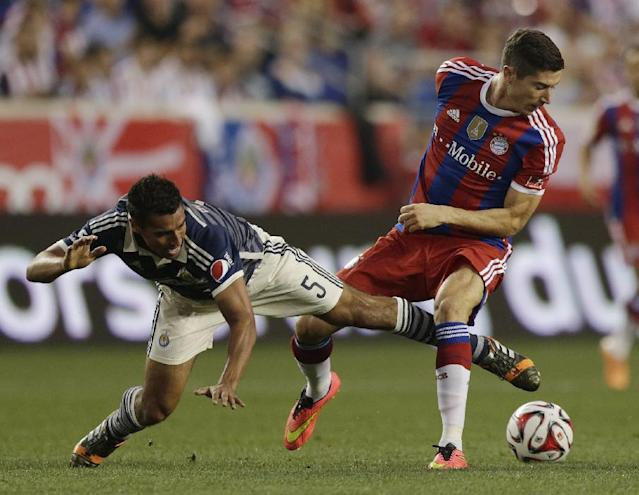 Chivas' Patricio Araujo, left, defends against Bayern Munich's Robert Lewandowski during the first half of an international friendly soccer match at Red Bull Arena, Thursday, July 31, 2014, in Harrison, N.J. (AP Photo/Julio Cortez)