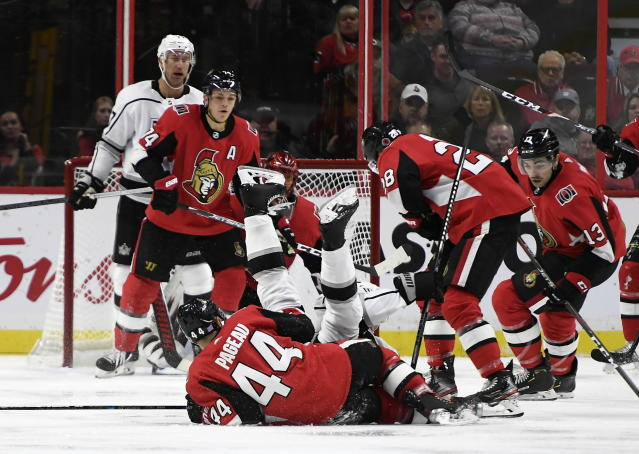 Los Angeles Kings left wing Dustin Brown (23) falls over Ottawa Senators center Jean-Gabriel Pageau (44) during second-period NHL hockey game action in Ottawa, Ontario, Thursday, Nov. 7, 2019. (Justin Tang/The Canadian Press via AP)