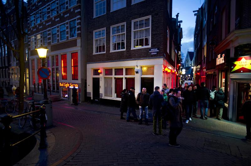 In this photo taken Tuesday, Feb. 4, 2014, tourists pack the narrow streets of Amsterdam's famed Red Light District near the entrance of the 'Red Light Secrets' museum, left, in Amsterdam. On any given evening, thousands of tourists visit Amsterdam's famed Red Light District, gawking at ladies in lingerie who work behind windows, making a living selling sex for money. Now a small educational museum is opening in heart of the district that aims to show reality from the other side of the glass. Organizer Melcher de Wind says the Red Light Secrets museum is for those who want to learn more about how the area works without actually visiting a prostitute. (AP Photo/Evert Elzinga)