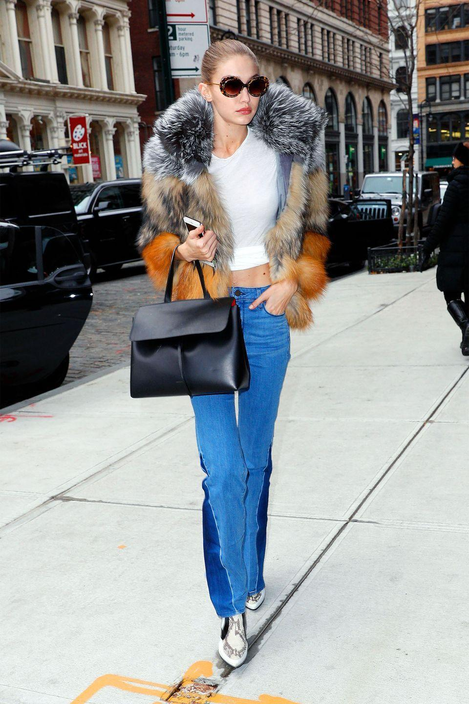 <p>In a colorblock fur coat, cropped white tee, two-toned flared jeans, white snakeskin boots, a Mansur Gavriel bag and round tortoise shell sunglasses by Krewe while out in New York.</p>