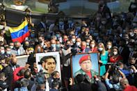 Venezuelan lawmakers carry portraits of revolutionary hero Simon Bolivar (L) and late socialist president Hugo Chavez (R) as they head to the National Assembly to be sworn in