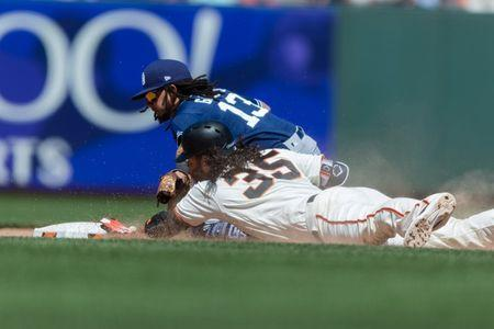 Jun 23, 2018; San Francisco, CA, USA; San Francisco Giants shortstop Brandon Crawford (35) slides in safe on a double as San Diego Padres shortstop Freddy Galvis (13) tries to take him in the eighth inning at AT&T Park. Mandatory Credit: John Hefti-USA TODAY Sports