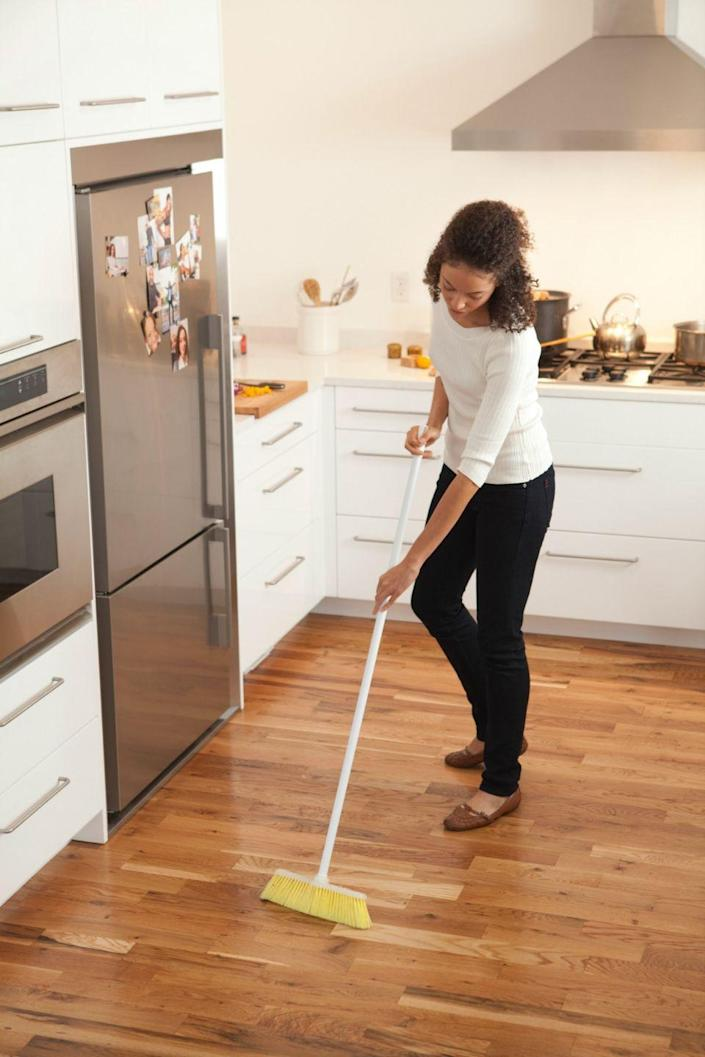 """<p>According to <em>Real Simple</em>,<a href=""""https://www.realsimple.com/home-organizing/cleaning/clean-hardwood-floors"""" rel=""""nofollow noopener"""" target=""""_blank"""" data-ylk=""""slk:vinegar is the best cleaner for hardwood floors"""" class=""""link rapid-noclick-resp""""> vinegar is the best cleaner for hardwood floors</a>. Melissa Witulski, the business operations manager for <a href=""""https://www.merrymaids.com/"""" rel=""""nofollow noopener"""" target=""""_blank"""" data-ylk=""""slk:Merry Maids"""" class=""""link rapid-noclick-resp"""">Merry Maids</a>, suggests making a solution by mixing a quarter cup of apple cider vinegar (or half a cup of white vinegar) with a gallon of warm water.</p><p>Start by sweeping the surface to remove any dust particles, then fill a bucket with the homemade vinegar solution. After that, begin cleaning, using a flat mop with a microfiber cover. Make sure you don't get your wood floors<em> too</em> wet, as water can remove the finish or potentially cause warping or deterioration.</p>"""
