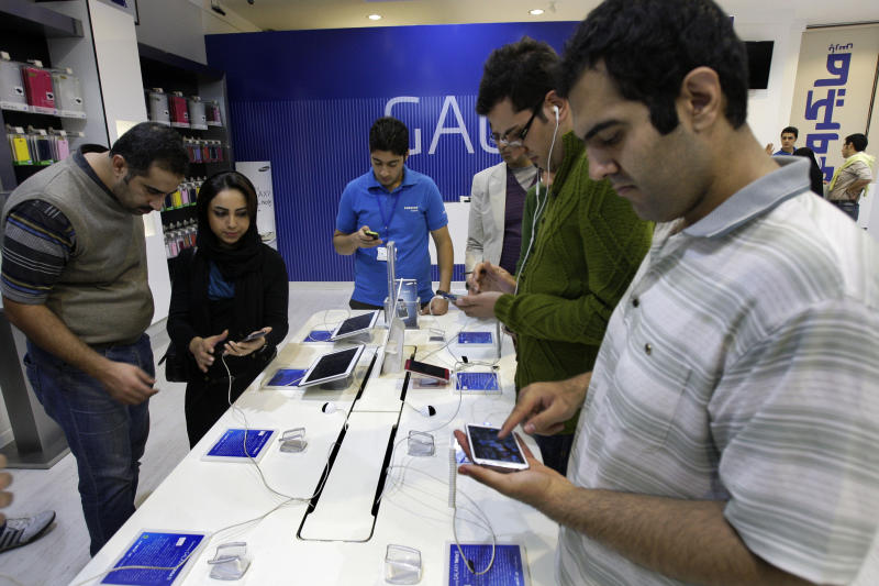Potential customers try out Samsung cell phones and tablet computers in a store, in Tehran, Iran, Thursday, Nov. 8, 2012. Sanctions-hit Iran has banned the import of foreign-made cars, laptops, and other 'luxury' goods in the hope of saving billions of dollars in hard currency, a state-owned newspaper reported Thursday. IRAN daily listed 75 products, from watches, home appliances and cell phones to coffee and toilet paper, that it said could no longer be purchased from abroad. But it says the ban does not apply to components used to produce the products. Iranian firms assemble many products including watches, laptops and cell phones. (AP Photo/Vahid Salemi)