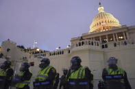 In this Wednesday, Jan. 6, 2021, photo, police form a line to guard the Capitol after violent rioters stormed the Capitol, in Washington. The top watchdog for the U.S. Capitol Police will testify to Congress for the first time about the department's broad failures before and during the Jan. 6 insurrection. Among them was missed intelligence and old weapons that officers didn't feel comfortable using. (AP Photo/John Minchillo)