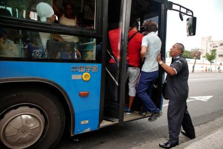 A public transportation inspector pushes people inside a bus in order to have its doors closed in Havana