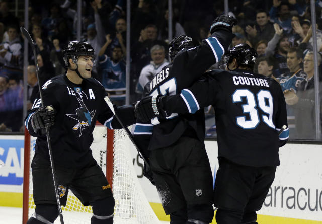 San Jose Sharks' Tommy Wingels, center, is hugged by teammates Patrick Marleau, left, and Logan Couture after Wingels' score against the Tampa Bay Lightning during the first period of an NHL hockey game on Thursday, Nov. 21, 2013, in San Jose, Calif. (AP Photo/Marcio Jose Sanchez)