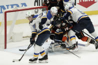 St. Louis Blues' Robert Thomas (18) moves the puck away from the net as Anaheim Ducks' Adam Henrique (14) is shoved by Blues' Colton Parayko (55) during the second period of an NHL hockey game Saturday, Jan. 30, 2021, in Anaheim, Calif. (AP Photo/Jae C. Hong)