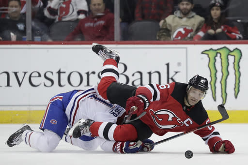New Jersey Devils defenseman Andy Greene (6) is tripped by Montreal Canadiens right wing Brendan Gallagher (11) during the second period of an NHL hockey game, Monday, Feb. 25, 2019, in Newark, N.J. (AP Photo/Julio Cortez)