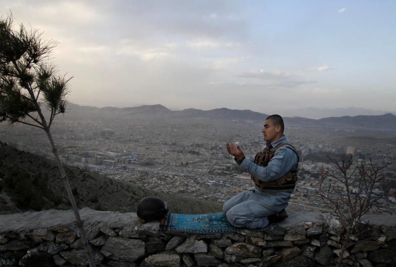 FILE - In this Sunday, March 31, 2013 file photo, an Afghan police man offers evening prayers on a hill overlooking Kabul, Afghanistan. As the country braces for next year's presidential election and the planned withdrawal of most foreign combat troops by the end of 2014, the panel urges the U.S. government and its allies to work harder to promote religious rights in the war-torn nation.  (AP Photo/Ahmad Jamshid, File)