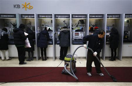 Customers use automated teller machines as a worker vacuums the floor at a branch of KB Kookmin Financial Group in Seoul January 21, 2014. REUTERS/Kim Hong-Ji