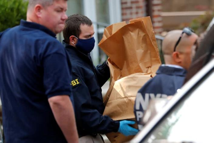 FBI officer removes evidence bags from a house, where police say bomb-making materials were found in New York