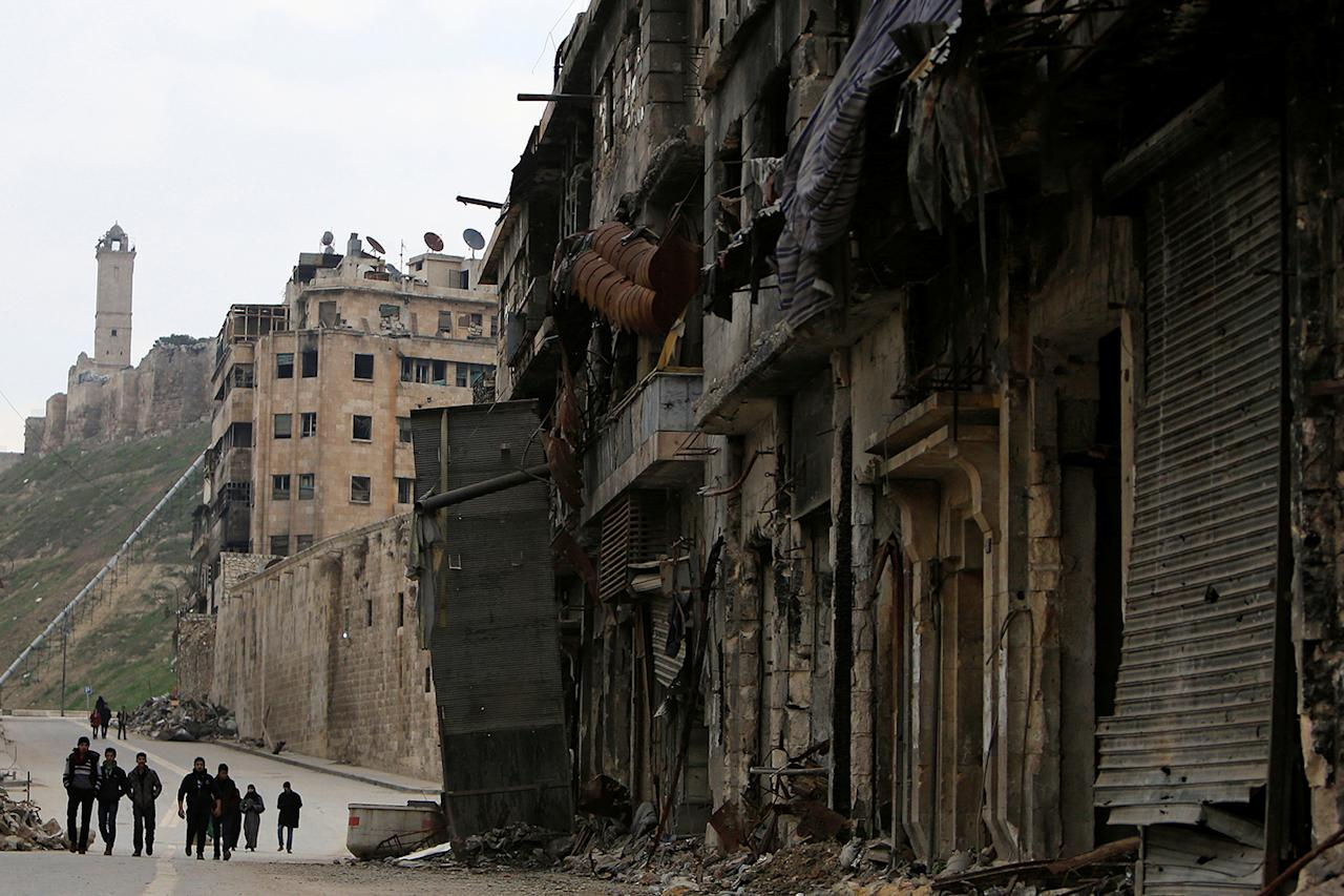<p>People walk past damaged shops in the Old City of Aleppo, Syria, Jan. 31, 2017. (Photo: Ali Hashisho/Reuters) </p>