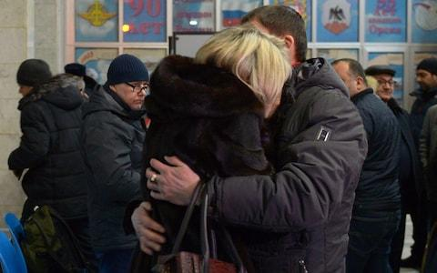 A man comforts a woman at Orsk airport, where loved ones of the victims gathered on Sunday - Credit: TASS/Barcroft Images