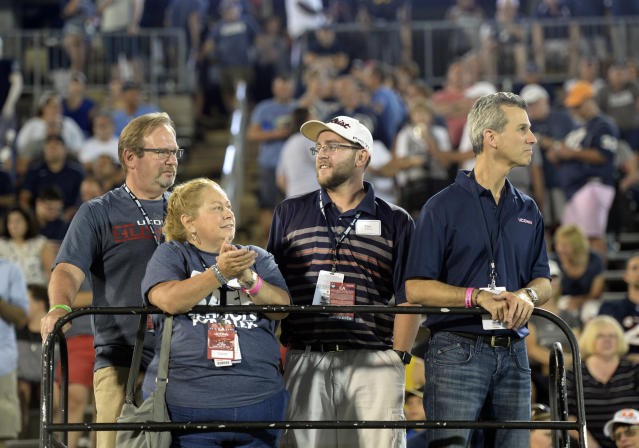 "Max Schachter, right, the father of Alex Schachterl, who was killed in the February shootings at Marjory Stoneman Douglas High School, watches the Connecticut marching band spell out the word ""Alex"" during the halftime show at the NCAA college football game Thursday, Aug. 30, 2018, in East Hartford, Conn. From left are Paul Goldberg, Alex's uncle Patti Goldberg, aunt; and Tim Goldberg, cousin. (AP Photo/Stephen Dunn)"