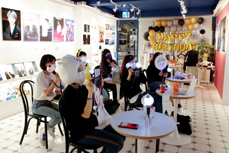 FILE PHOTO: Fans of K-pop idol boy band BTS enjoy as they watch a live streaming online concert, wearing a protective masks at a cafe, in Seoul