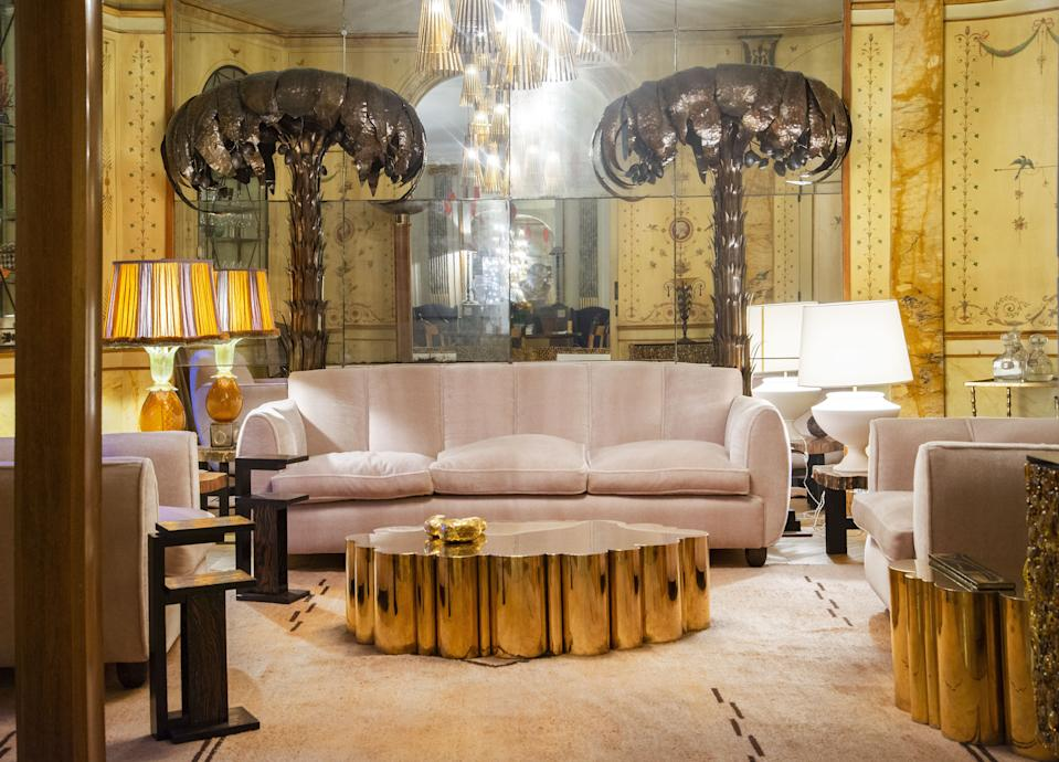 """<div class=""""caption""""> In the small salon, the Cloud Table is by Kam Tin and the decorative wall painting is original and from 1910. The sofa and armchairs are from 1930 by an Italian architect and designer of Danish origin, Guglielmo Ulrich. The palm trees are in bronze patinated brass and the little side tables are by French designer André Sornay from the 1940s. The Murano glass lamp is also from the 1940s, while the plaster light is from the 1960s. The low table is by Belgian designer Ado Chale. </div>"""