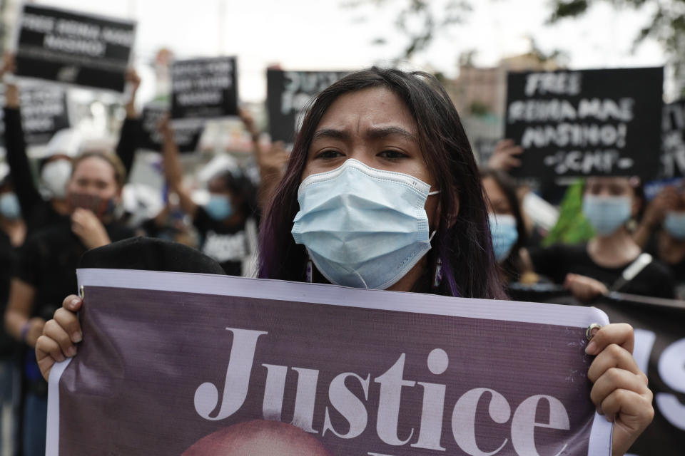 Protesters hold slogans during a rally outside Manila's North Cemetery, Philippines where detained left-wing activist Reina Mae Nasino attends funeral rites of her three-month-old firstborn named River on Friday Oct. 16, 2020. Left-wing groups on Friday decried as brutal the treatment of a detained activist, who was allowed by a Manila court to attend her baby's burial but was restrained with handcuffs, a sweltering protective suit and swarms of armed escorts as she quietly wept. (AP Photo/Aaron Favila)
