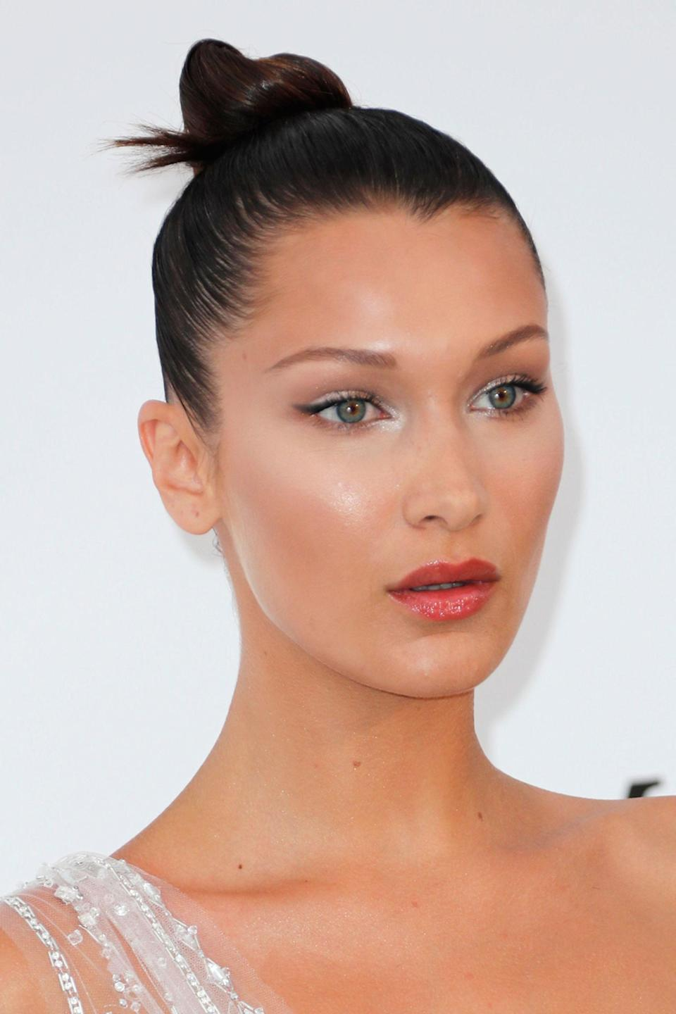 """<p>The supermodel wore her hair slicked back into a tight bun and created a dewy look with glistening highlighter on her cheekbones, chin and forehead - slightly <a rel=""""nofollow noopener"""" href=""""http://www.harpersbazaar.co.uk/beauty/make-up-nails/news/a40575/highlight-trick-kim-kardashian-make-up-artist-mario-dedivanovic"""" target=""""_blank"""" data-ylk=""""slk:off-centre"""" class=""""link rapid-noclick-resp"""">off-centre</a> for a more natural look. </p>"""
