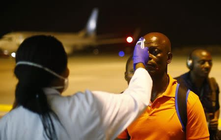 A health worker checks the temperature of a man arriving at Bata Airport, January 14, 2015. REUTERS/Amr Abdallah Dalsh