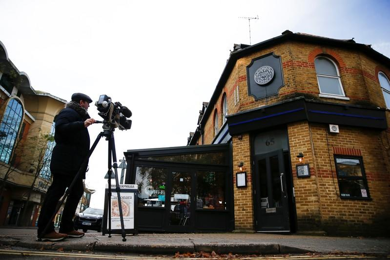 A television crew stand outside of a Pizza Express restaurant in Woking