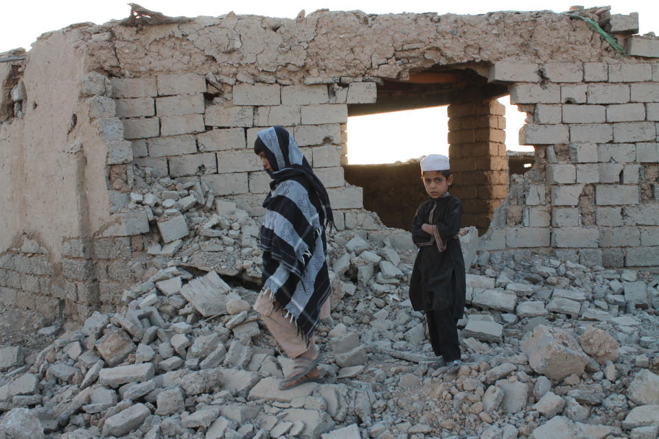 Boys walk past a house damaged by airstrikes two weeks earlier during a fight between government forces and the Taliban, in Lashkar Gah, Helmand province, southwestern Afghanistan, Saturday, Aug. 21, 2021. (AP Photo/Abdul Khaliq)