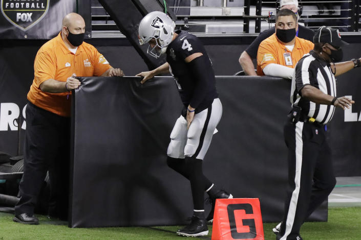 Las Vegas Raiders quarterback Derek Carr (4) limps on the sidelines after a play against the Los Angeles Chargers during the first half of an NFL football game, Thursday, Dec. 17, 2020, in Las Vegas. (AP Photo/Isaac Brekken)