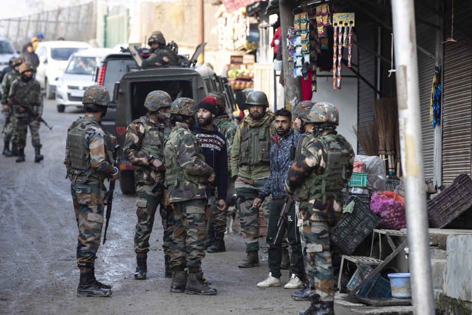 Indian security officers interrogate civilians near the site of an attack on the outskirts of Srinagar, Indian controlled Kashmir, Thursday, Nov. 26, 2020. Anti-India rebels in Indian-controlled Kashmir Thursday killed two soldiers in an attack in the disputed region's main city, the Indian army said.(AP Photo/Mukhtar Khan)