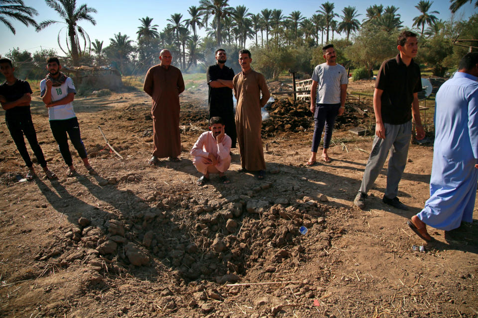 People inspect a crater caused by a deadly Katyusha rocket attack near international airport in Baghdad, Iraq, Tuesday, Sept. 29, 2020. Several Iraqi civilians were killed and two severely wounded Monday after the rocket hit near Baghdad airport, Iraq's military said. It was the first time in months an attack caused civilian casualties. (AP Photo/Khalid Mohammed)