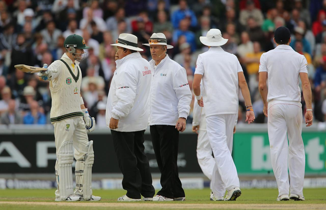 Australia captain Michael Clarke speaks to Umpire Marais Erasmus and Tony Hill as they stop play for bad light, during day four of the Third Investec Ashes test match at Old Trafford Cricket Ground, Manchester.