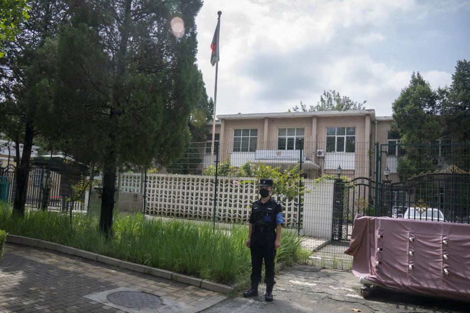The Afghanistan flag flies from a flagpole as a Chinese security officer stands guard outside the Afghanistan Embassy in Beijing on Aug. 20, 2021. In the U.S. departure from Afghanistan, China has seen the realization of long-held hopes for a reduction of the influence of a geopolitical rival in what it considers its backyard. Yet, it is also deeply concerned that the very withdrawal could bring instability to that backyard - Central Asia - and possibly even spill over the border into China itself in its heavily Muslim northwestern region of Xinjiang. (AP Photo/Mark Schiefelbein)