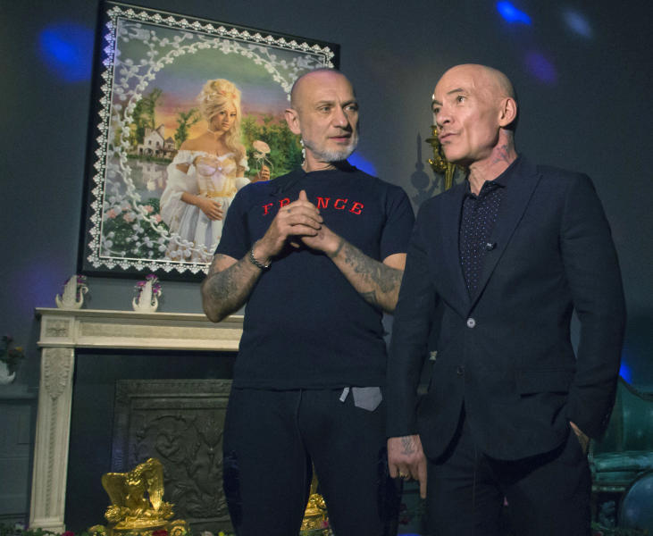 French artists Pierre Commoy, left, and Gilles Blanchard, known as Pierre et Gilles, pose inside their installation at the Gobelins Gallery in Paris, Monday, April 7, 2014. Pierre Commoy and Gilles Blanchard, who have established a strong reputation in Europe and beyond for shock ever since their stylized, hand-painted homoerotic photos first appeared nearly 40 years ago. Today, their iconic images of stars such as Madonna, Kylie Minogue, Mick Jagger and Catherine Deneuve which appear alongside naked gay porn stars in glittering and fantastical scenes line coffee-tables the world over and have titillated millions. (AP Photo/Michel Euler)