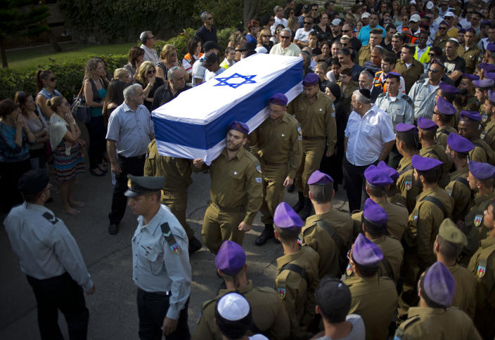 Israeli soldiers carry the flagged wrapped coffin of Staff Sergeant Gabriel Koby, during his funeral at the military cemetery in Haifa ,Israel, Monday, Sept. 23, 2013. Koby, 20, was shoot and killed by an unknown gunmen in the biblical city of Hebron in the West Bank on Sunday, and troops are searching for the shooter, the military said. It was the second soldier killed since the weekend when a Palestinian killed an Israeli soldier with the intention of trading the body for his brother who is jailed for shooting attacks. (AP Photo/Ariel Schalit)