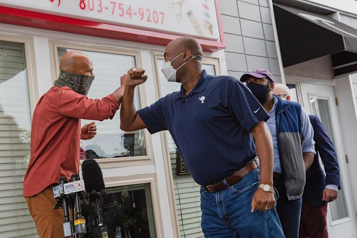 Jaime Harrison greets Common during a campaign event outside a barbershop in Columbia, South Carolina, U.S., on Monday, Oct. 26, 2020. (Photographer Micah Green/Bloomberg)