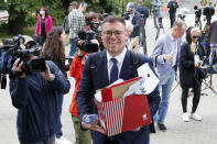 Russian lawyer Vladimir Voronin carries documents after a break in a court session in front of Moscow Court in Moscow, Russia, Wednesday, June 9, 2021. A court is expected to outlaw the organizations founded by Russian opposition leader Alexei Navalny. Prosecutors have asked the Moscow City Court to designate Navalny's Foundation for Fighting Corruption and his sprawling network of regional offices as extremist organizations. The extremism label also carries lengthy prison terms for activists who have worked with the organizations, anyone who donated to them, and even those who simply shared the groups' materials. (AP Photo/Alexander Zemlianichenko)
