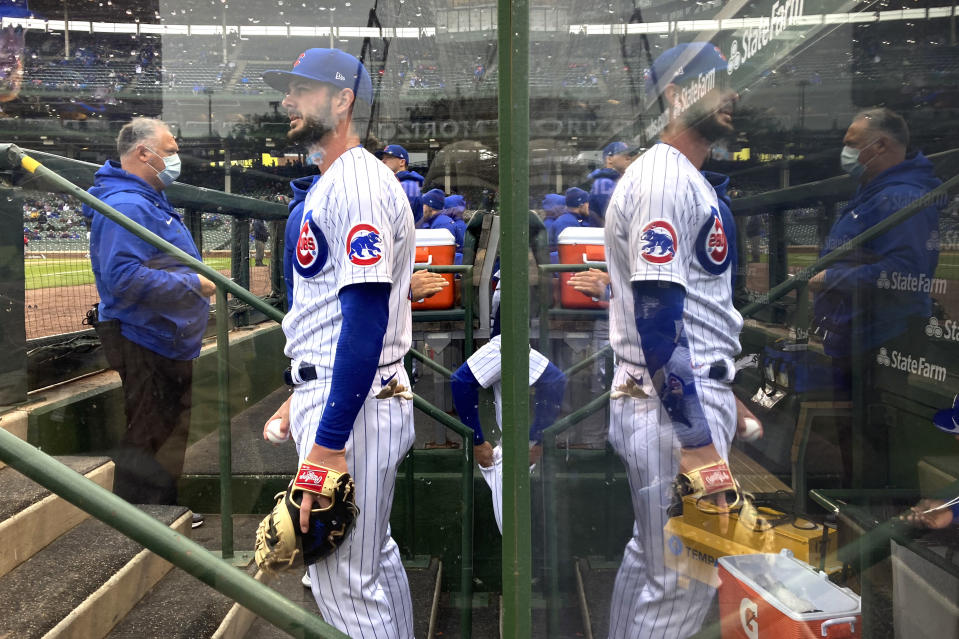 FILE - Chicago Cubs' Kris Bryant is reflected in a COVID-19 protective plexiglass wall before a baseball game against the Cincinnati Reds in Chicago, in this May 29, 2021, file photo. Bryant's versatility, while producing offensive numbers that belong alongside his NL MVP season in 2016, is a big reason why Chicago is on top of the NL Central once again, helping the Cubs go on a 21-9 run while dealing with a rash of injuries. (AP Photo/Charles Rex Arbogast, File)