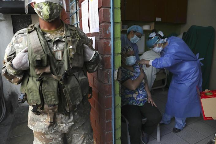 A soldier stands guard as a woman is given a COVID-19 shot