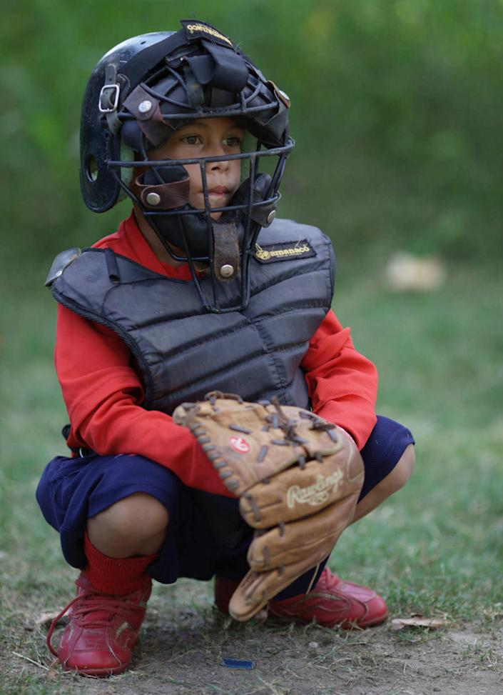 In this Oct. 25, 2012, a young baseball catcher attends a baseball school in Maracay, Venezuela. Many of the boys are inspired by the example of Detroit Tigers slugger Miguel Cabrera, who learned the game on this very field. Their baseball school in the poor neighborhood where Cabrera grew up is one of many across Venezuela, a web for training young ballplayers that has made the country a powerhouse in the U.S. major leagues. (AP Photo/Ariana Cubillos)
