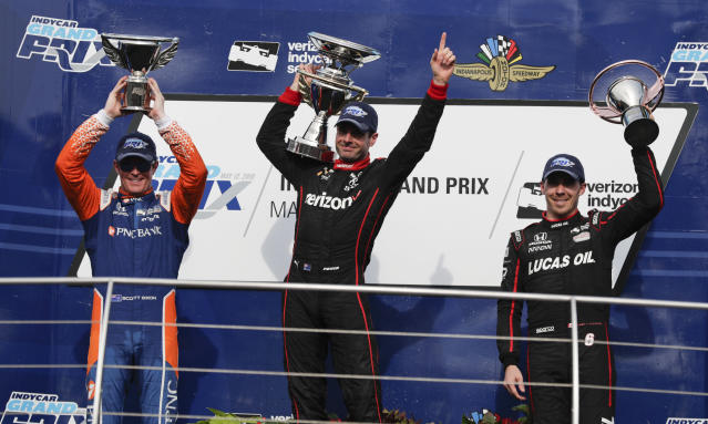 Will Power, center, of Australia, celebrates after winning the IndyCar Grand Prix auto race, next to second-place Scott Dixon, left, of New Zealand, and third-place Robert Wickens, of Canada, at Indianapolis Motor Speedway on Saturday, May 12, 2018, in Indianapolis. (AP Photo/Michael Conroy)