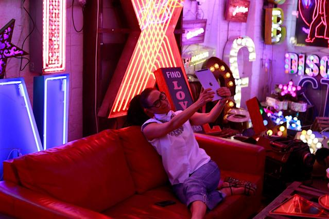<p>A woman takes a picture of neon signs while sitting on a sofa in God's Own Junkyard gallery and cafe in London, Britain, May 13, 2017. (Photo: Russell Boyce/Reuters) </p>