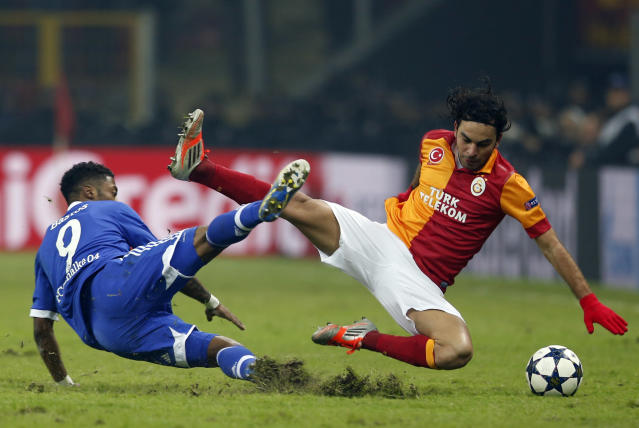 Galatasaray's Selcuk Inan (R) and Schalke 04's Michel Bastos (L) fall during their Champions League soccer match at Turk Telekom Arena in Istanbul February 20, 2013. REUTERS/Murad Sezer (TURKEY - Tags: SPORT SOCCER TPX IMAGES OF THE DAY) - RTR3E1TP