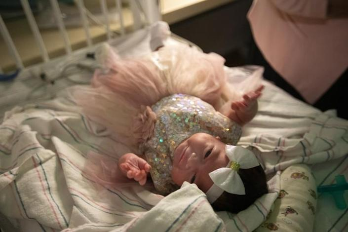 LOMA LINDA, CA - Septmber 7, 2020: Monica Ramirez, 38, of Corona dressed her newborn daughter Emiliana Ramirez in a new dress and a bow on her head inside the NICU at LomaLindaUniversityChildren's Hospital on Thursday, Aug. 27, 2020 in Loma Linda, CA. Monica was pregnant and became Covid positive. She gave birth to her daughter while in a coma at LomaLindaUniversityChildren's Hospital during the global coronavirus pandemic. This afternoon Emiliana is going home for the first time. (Francine Orr / Los Angeles Times)