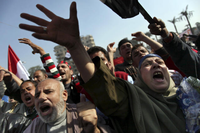 """Egyptian protesters chant anti-Muslim Brotherhood slogans as they attend a rally in Tahrir Square, in Cairo, Egypt, Friday, Nov. 30, 2012. Egypt's opposition has called for a major rally Friday in Cairo's Tahrir Square, where some demonstrators have camped out in tents since last week to protest decrees that President Mohammed Morsi issued to grant himself sweeping powers. Hundreds gathered in the plaza for traditional Friday prayers, then broke into chants of """"The people want to bring down the regime!"""" — echoing the refrain of the Arab Spring revolts, but this time against a democratically elected leader. Other cities around Egypt braced for similar protests.(AP Photo/Khalil Hamra)"""